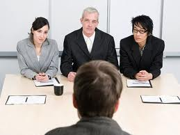Panel interview in a bank, with three interviewers, two male and one female, and a young job applicant sitting in front of them
