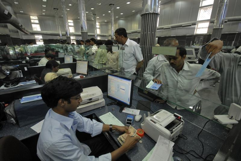 A buys banking center in India. We can see a teller at the desk counting money from the client